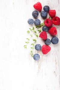 41734520 - berries on white wooden background. summer or spring organic berry over wood. raspberries, blueberry and thyme. helthy food, gardening, harvest concept. copy space.